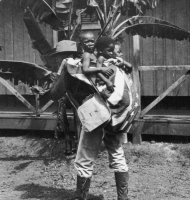 """This 1899 image, """"Uncle Sam's Burden,"""" shows a U.S. soldier carrying three dark-skinned children (representing the Philippines, Puerto Rico, and Cuba) in a backpack made out of the U.S. flag."""