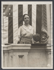 "Photograph of Winifred Huck using the ""carbon button"" microphones on the rostrum in 1922."