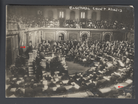"This photograph of the 1913 electoral vote count includes some ghostly images. The head of House Speaker <a href=""/People/Detail/11000?ret=True"" title=""Champ Clark"">Champ Clark</a>, seated next to Senator Bacon on the rostrum, seems to float. Toward the bottom appears a Representative so transparent that his papers are visible through his head."