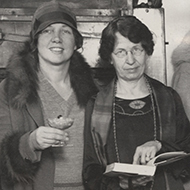 Two Women Holding a Cookbook and a Dessert