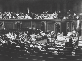 Jeannette Rankin addresses the House for her first speech on August 7, 1917. In the center foreground of the image, Pennsylvania Congressman Joseph Hampton Moore questions Rankin at the conclusion of her speech.