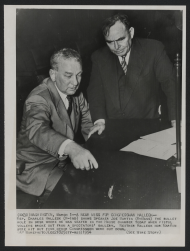 Representative Charles Halleck of Indiana showed Speaker Joe Martin the bullet hole in the desk he was occupying