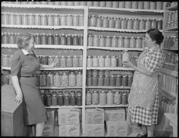 Two Women Admiring Preserved Food in a Pantry