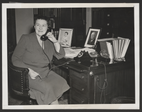 Representative Mary Norton sits at her desk and talks on the phone
