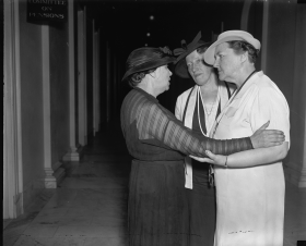 Three women in Congress confer in the hallway