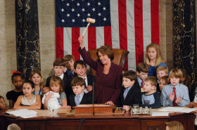Nancy Pelosi on the rostrum holding up a gavel and surrounded by children