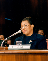 Senator Carol Moseley-Braun sits in front of a microphone