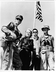 Accompanied by U.S. Marine officers, Senator Margaret Chase Smith tours a U.S. military facility. Smith was the first woman to serve on the Armed Services Committee in both the House and the Senate.